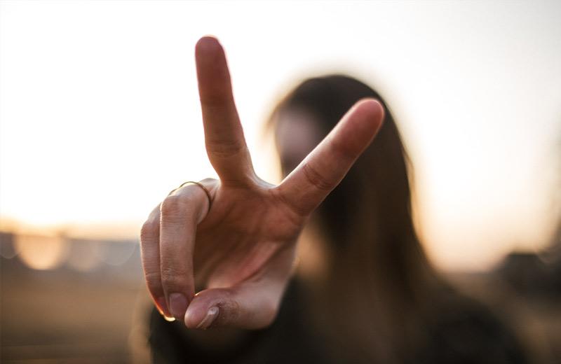 Eine Frau zeigt das Victoryzeichen